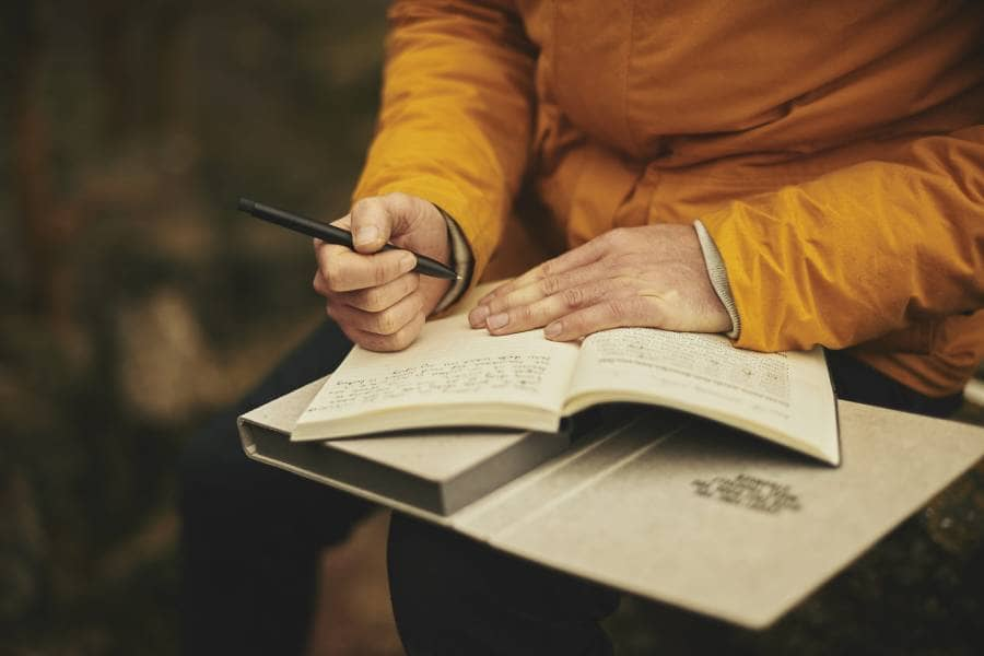 hands-writing-jacket-yellow-notebook-pen-TripOrTrek